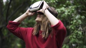 Κορίτσι στο κόκκινο που φορά τα γυαλιά VR σε ένα πάρκο απόθεμα βίντεο