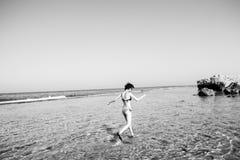 Κορίτσι στο μαγιό που οργανώνεται από το νερό, γραπτό Στοκ Εικόνες