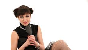 Κορίτσι στο μαύρα τραγούδι και το Uusing φορεμάτων μια χτένα φιλμ μικρού μήκους