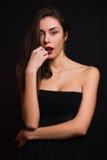 Κορίτσι στο μαύρο φόρεμα που εξετάζει seductively τη κάμερα Στοκ Φωτογραφία