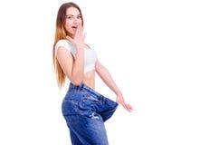 Κορίτσι στο μεγάλο μέγεθος τζιν παντελόνι σε ένα άσπρο υπόβαθρο Στοκ Φωτογραφίες
