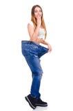 Κορίτσι στο μεγάλο μέγεθος τζιν παντελόνι σε ένα άσπρο υπόβαθρο Στοκ Εικόνες