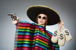 Κορίτσι στο μεξικάνικα poncho περίστροφο και τα χρήματα εκμετάλλευσης Στοκ εικόνα με δικαίωμα ελεύθερης χρήσης