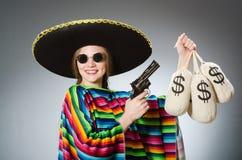 Κορίτσι στο μεξικάνικα poncho περίστροφο και τα χρήματα εκμετάλλευσης Στοκ Φωτογραφία