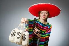 Κορίτσι στο μεξικάνικα poncho περίστροφο και τα χρήματα εκμετάλλευσης Στοκ Εικόνες