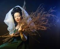Κορίτσι στο μεσαιωνικό φόρεμα με τη δέσμη των ραβδιών Στοκ Φωτογραφία