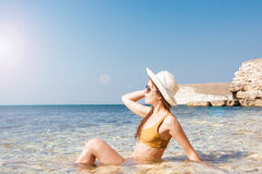 Κορίτσι στο μπικίνι, τα γυαλιά και το καπέλο στο σαφές θαλάσσιο νερό Στοκ εικόνες με δικαίωμα ελεύθερης χρήσης