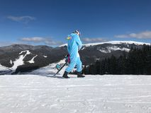 Κορίτσι στο μπλε, ρόδινο kigurumi πυτζαμών μονοκέρων υπαίθριο με το σνόουμπορντ στην έκθεση σκι στα βουνά χιονιού Στοκ Εικόνα
