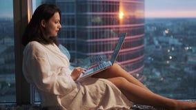 Κορίτσι στο μπουρνούζι που στηρίζεται κοντά στο παράθυρο σε ένα υψηλό πάτωμα σε ένα ξενοδοχείο κορίτσι blogger πίσω από το lap-to απόθεμα βίντεο