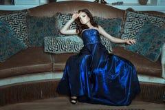 Κορίτσι στο μπλε και λαμπρό φόρεμα που θέτει να βρεθεί τον καναπέ Στοκ Εικόνα