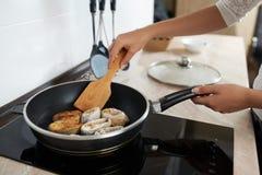 Κορίτσι στο νόστιμο τηγάνι ψαριών τηγανητών κουζινών Στοκ Φωτογραφία