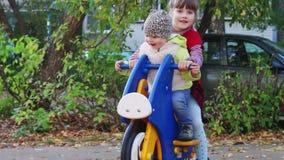 Κορίτσι στο ξύλινο παιχνίδι μοτοσικλετών στην παιδική χαρά με την αδελφή φιλμ μικρού μήκους