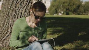 Κορίτσι στο πάρκο και το PC ταμπλετών χρήσης φιλμ μικρού μήκους