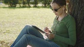 Κορίτσι στο πάρκο και το PC ταμπλετών χρήσης απόθεμα βίντεο