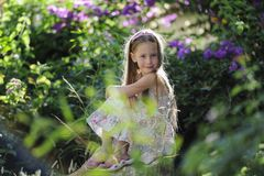 Κορίτσι στο πάρκο μεταξύ των λουλουδιών στοκ εικόνα