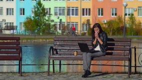 Κορίτσι στο πάρκο σε έναν πάγκο, που λειτουργεί σε ένα lap-top Έχει ένα κρύο, σκουπίζει τη μύτη της με ένα χαρτομάνδηλο απόθεμα βίντεο