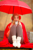 Κορίτσι στο πάρκο φθινοπώρου που απολαμβάνει το ζεστό ποτό Στοκ εικόνα με δικαίωμα ελεύθερης χρήσης