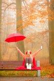 Κορίτσι στο πάρκο φθινοπώρου που απολαμβάνει το ζεστό ποτό Στοκ Εικόνα