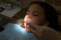 Κορίτσι στο παιδιατρικό γραφείο οδοντιάτρων, επεξεργασία των δοντιών μωρών Στοκ Εικόνες
