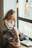 Κορίτσι στο παράθυρο με ένα φλιτζάνι του καφέ και ένα περιοδικό Στοκ φωτογραφίες με δικαίωμα ελεύθερης χρήσης