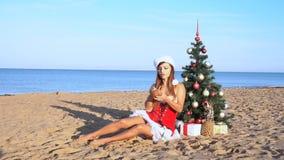 Κορίτσι στο παραθαλάσσιο θέρετρο στα ενδύματα Χριστουγέννων για το νέο έτος στους τροπικούς κύκλους 1 φιλμ μικρού μήκους