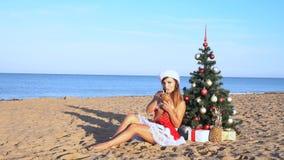 Κορίτσι στο παραθαλάσσιο θέρετρο στα ενδύματα Χριστουγέννων για το νέο έτος 1 απόθεμα βίντεο