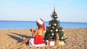 Κορίτσι στο παραθαλάσσιο θέρετρο στα ενδύματα Χριστουγέννων για το νέο έτος στους τροπικούς κύκλους 1 απόθεμα βίντεο
