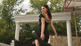 Κορίτσι στο πολύ μαύρο φόρεμα που περιβάλλει γύρω από την φιλμ μικρού μήκους