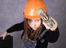 Κορίτσι στο πορτοκαλί εργαλείο σφυριών εκμετάλλευσης φανέλλων κρανών ασφάλειας στοκ εικόνα