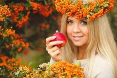 Κορίτσι στο πορτοκαλί στεφάνι με την κόκκινη Apple διαθέσιμη Στοκ Εικόνα