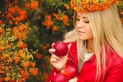 Κορίτσι στο πορτοκαλί στεφάνι με την κόκκινη Apple διαθέσιμη Στοκ Φωτογραφίες