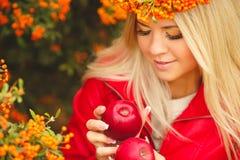 Κορίτσι στο πορτοκαλί στεφάνι με την κόκκινη Apple διαθέσιμη Στοκ Εικόνες