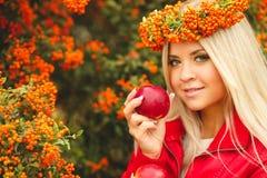 Κορίτσι στο πορτοκαλί στεφάνι με την κόκκινη Apple διαθέσιμη Στοκ Φωτογραφία