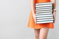 Κορίτσι στο πορτοκαλί φόρεμα που κρατά έναν σωρό των βιβλίων Στοκ φωτογραφία με δικαίωμα ελεύθερης χρήσης