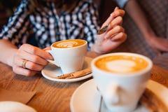 Κορίτσι στο πουκάμισο καρό που κρατά ένα φλυτζάνι του cappuccino Στοκ φωτογραφία με δικαίωμα ελεύθερης χρήσης