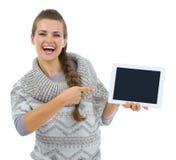 Κορίτσι στο πουλόβερ που δείχνει στην κενή οθόνη PC ταμπλετών Στοκ φωτογραφία με δικαίωμα ελεύθερης χρήσης