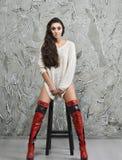 Κορίτσι στο πουλόβερ και τις μπότες Στοκ Φωτογραφία