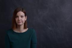 Κορίτσι στο πράσινο φόρεμα στο σχολικό πίνακα Στοκ Εικόνες