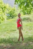 Κορίτσι στο ρόδινο κοστούμι που κάνει τη γυμναστική στο δάσος Στοκ Εικόνες