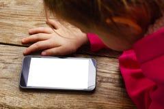 Κορίτσι στο ρόδινο πουλόβερ που βρίσκεται στο πάτωμα και που εξετάζει το κινητό τηλέφωνο Στοκ φωτογραφία με δικαίωμα ελεύθερης χρήσης