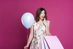 Κορίτσι στο φόρεμα με τις τσάντες και το μπαλόνι δώρων στοκ εικόνες με δικαίωμα ελεύθερης χρήσης