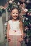Κορίτσι στο φόρεμα που στέκεται κοντά στο χριστουγεννιάτικο δέντρο και που κρατά τα δώρα Στοκ φωτογραφία με δικαίωμα ελεύθερης χρήσης