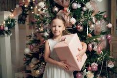 Κορίτσι στο φόρεμα που στέκεται κοντά στο χριστουγεννιάτικο δέντρο και που κρατά τα δώρα Στοκ Φωτογραφίες