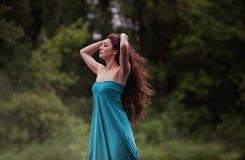 Κορίτσι στο φόρεμα που στέκεται με το δασικό υπόβαθρο Στοκ φωτογραφία με δικαίωμα ελεύθερης χρήσης