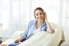 Κορίτσι στο χαμόγελο ακουστικών που ακούει τη συνεδρίαση μουσικής εσωτερική στοκ εικόνες