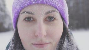 Κορίτσι στο χαμόγελο ξύλων που εξετάζει τη κάμερα, που καλύπτεται με το χιόνι μετά από μια θύελλα χιονιού Στοκ Εικόνες
