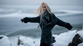 Κορίτσι στο χιόνι στο χειμερινό υπόβαθρο Στοκ Εικόνες