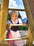 Κορίτσι στο dirndl που αναρριχείται σε μια φωτογραφική διαφάνεια Στοκ εικόνες με δικαίωμα ελεύθερης χρήσης