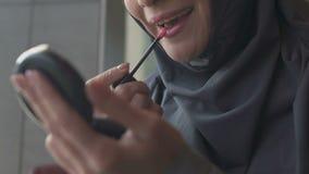 Κορίτσι στο hijab που εφαρμόζει το κραγιόν, θρησκευτική απαγόρευση στα καλλυντικά για τις ισλαμικές γυναίκες απόθεμα βίντεο