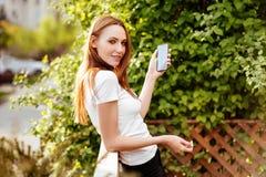 Κορίτσι στο smartphone πάρκων iwith στοκ εικόνες